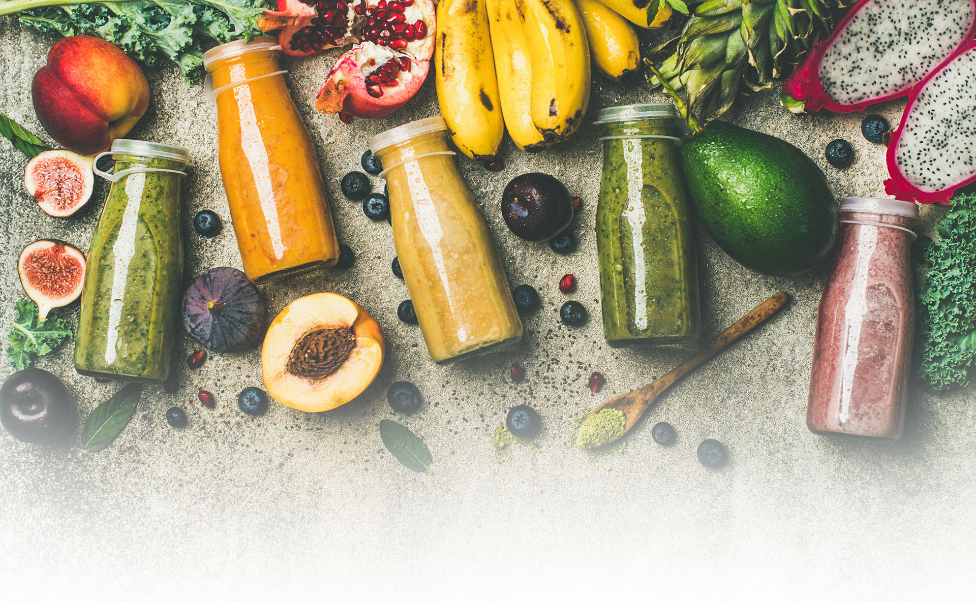 Colorful smoothies in bottles with fresh tropical fruit, copy space