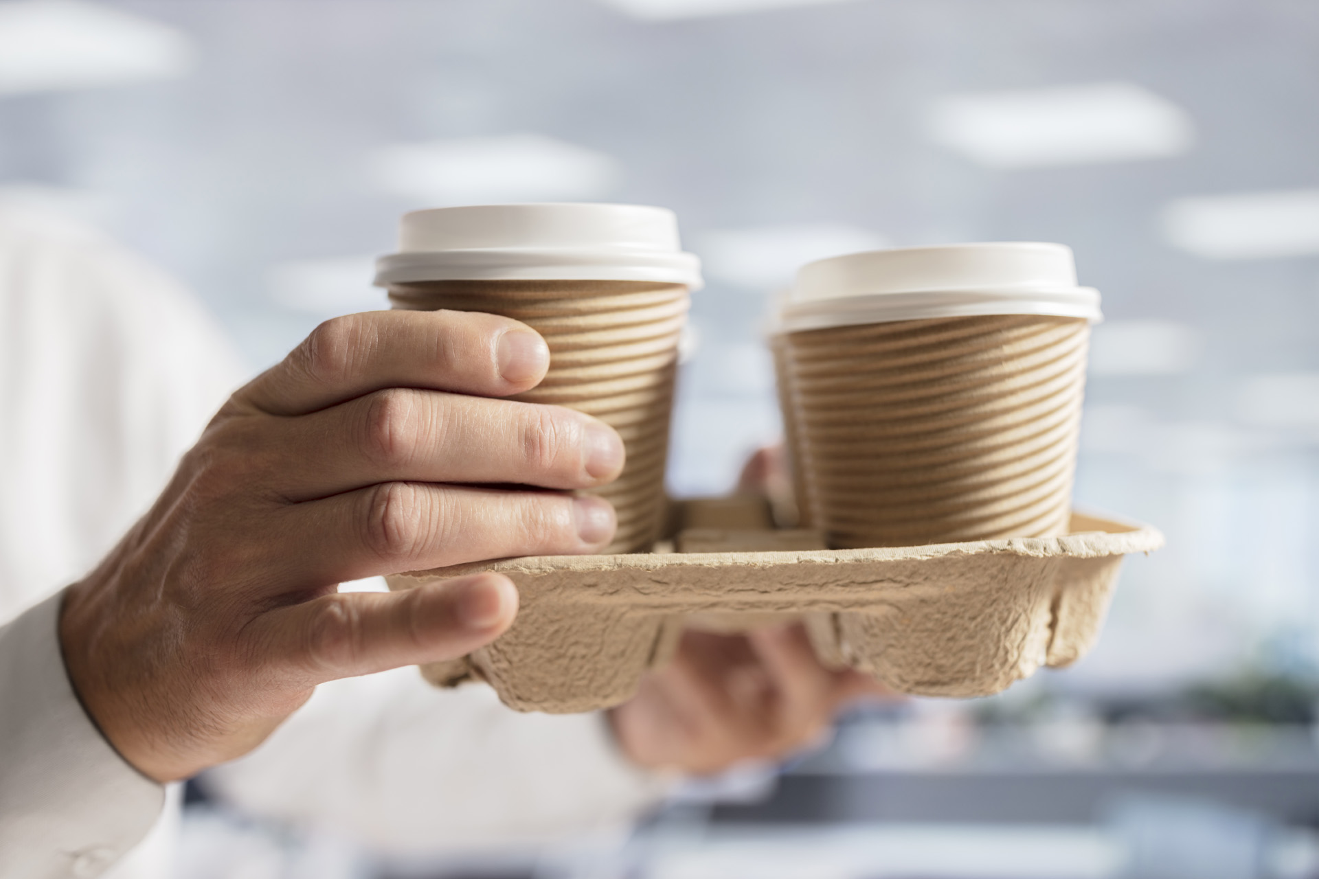 Businessman carrying coffee take out disposable cups in office f
