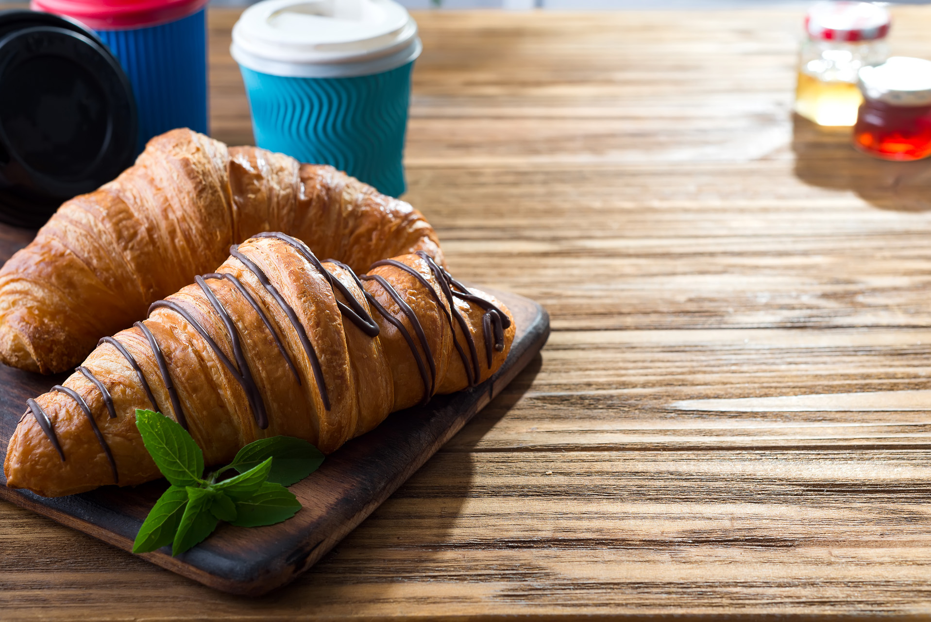 cups of coffee and two croissants on the street in Croissant Cafe. Inscripton on cup - Croissant Cafe. Breakfast to go