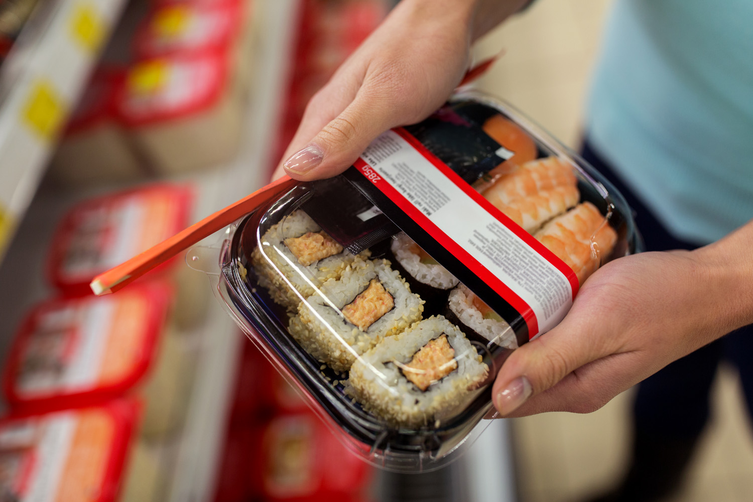 hands with sushi pack at grocery or supermarket