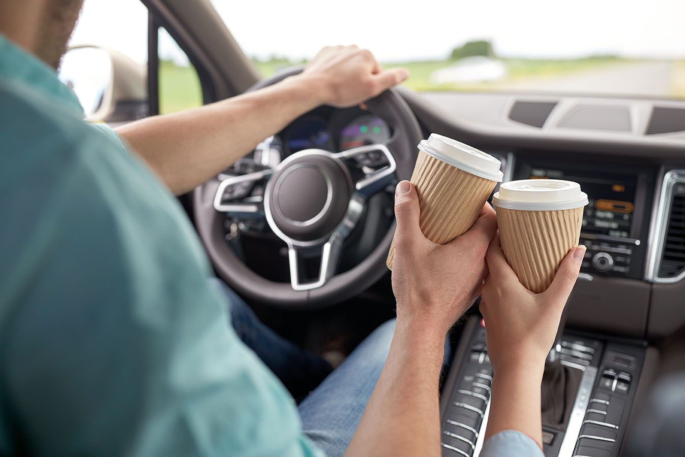 close up of couple driving in car with coffee cups
